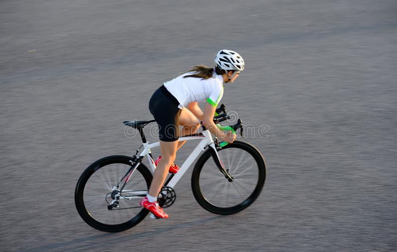 Young Woman Riding Road Bicycle on Free Street in the City at Sunset. Healthy Lifestyle and Sport Concept. Young Woman Cyclist Riding Road Bicycle on the Free stock images