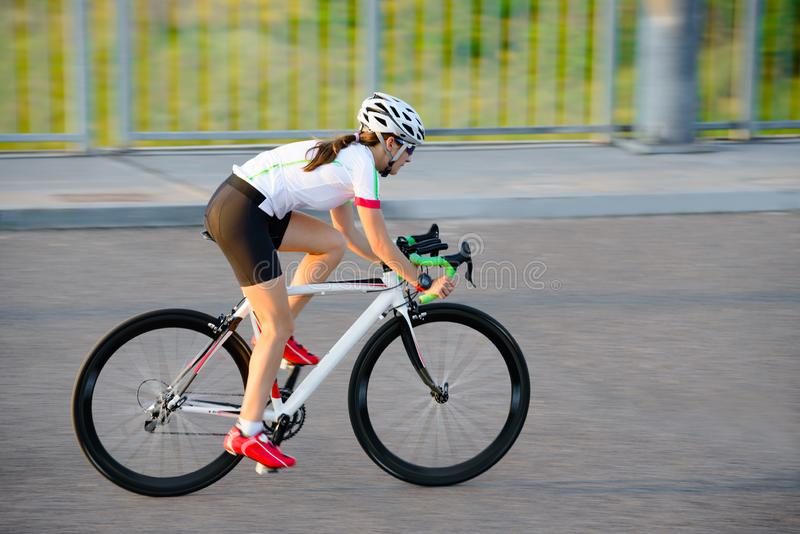 Young Woman Riding Road Bicycle on Free Street in the City at Sunset. Healthy Lifestyle and Sport Concept. Young Woman Cyclist Riding Road Bicycle on the Free stock photo