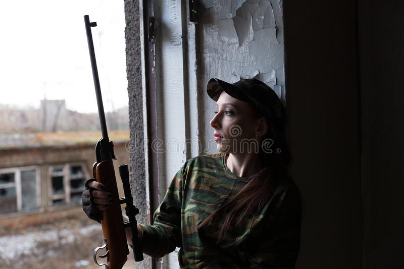 A young woman with a rifle in uniform at the window looking at the street. The woman sniper in a green suit and cap. A young woman with a rifle at the window royalty free stock photography