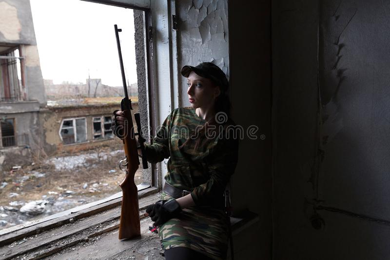 A young woman with a rifle in uniform at the window looking at the street. The woman sniper in a green suit and cap. A young woman with a rifle at the window royalty free stock photo