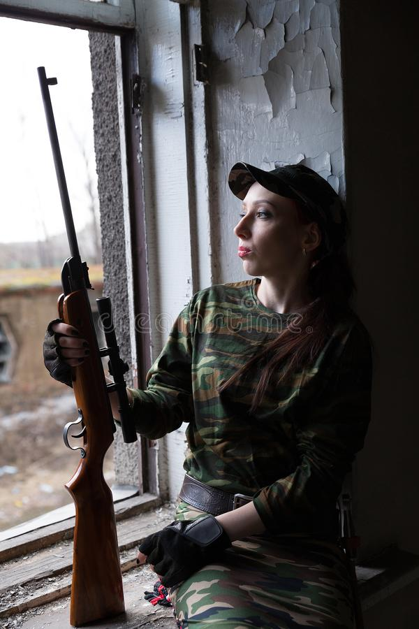 A young woman with a rifle in uniform at the window looking at the street. The woman sniper in a green suit and cap. A young woman with a rifle at the window stock photography