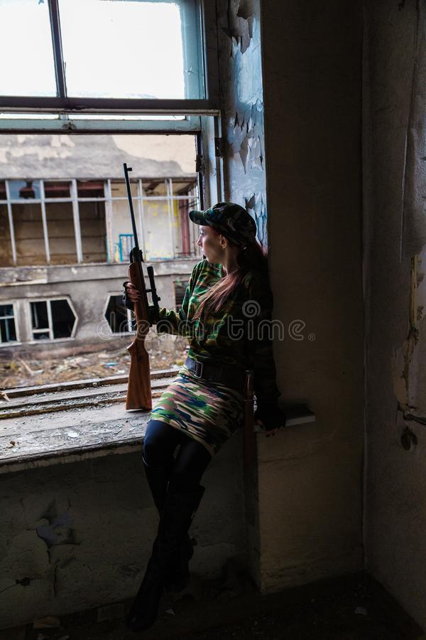 A young woman with a rifle in uniform at the window looking at the street. The woman sniper in a green suit and cap. A young woman with a rifle at the window royalty free stock photos