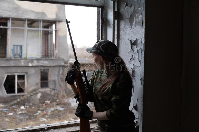 A young woman with a rifle in uniform at the window looking at the street. The woman sniper in a green suit and cap. A young woman with a rifle at the window royalty free stock image