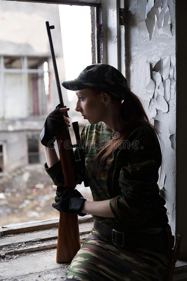 A young woman with a rifle in uniform at the window looking at the street. The woman sniper in a green suit and cap. A young woman with a rifle at the window stock images