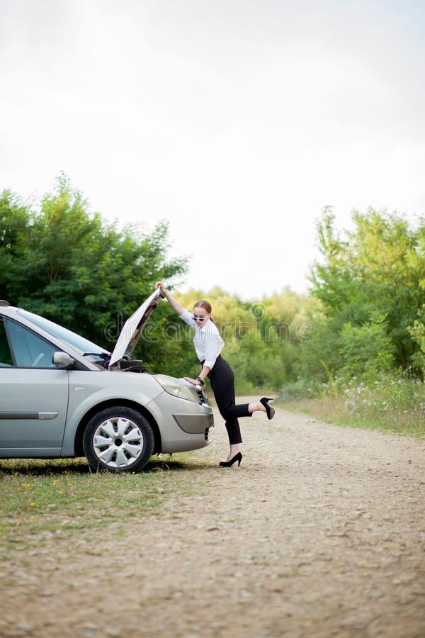 Young woman by the roadside after her car has broken down She opened the hood to see the damage stock photo