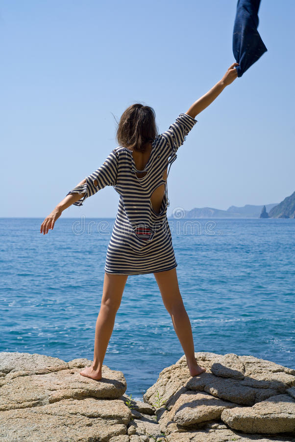 Young woman on rock 3. The young woman in old striped vest stands on rock at sea stock photography