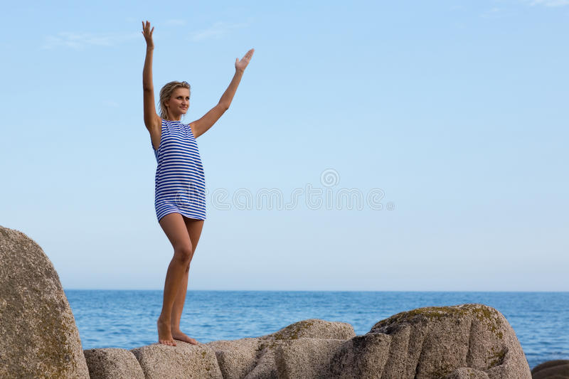 Young woman on a rock by the sea. Young woman in the striped shirt on a rock by the sea stock photo