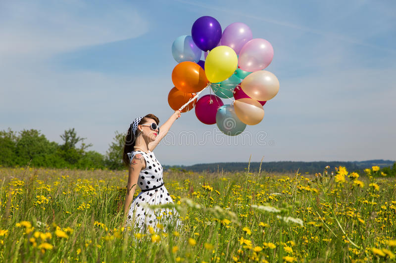 Young woman with a rockabilly dot dress and a lot of balloons in. Young woman with a white rockabilly dot dress and a lot of colorful balloons in the meadow stock photography