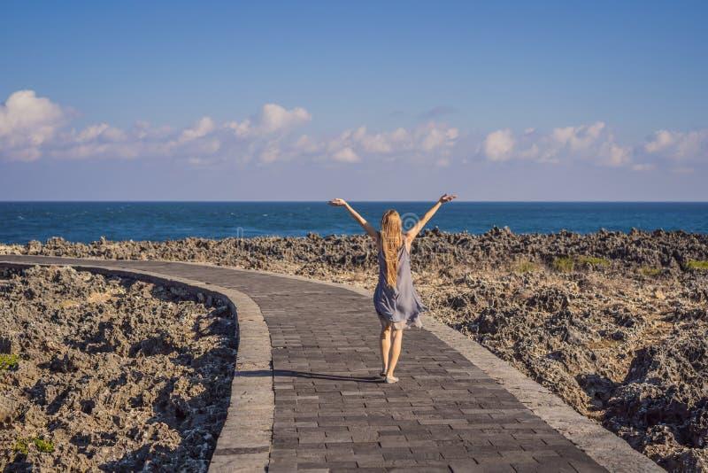 Young woman on the rocks in Bali, Nusadua, Waterbloom Fountain.  royalty free stock image