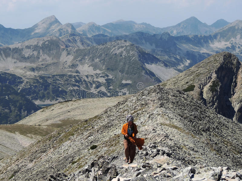 Young Woman in Rocky Mountain. Young woman high on a rocky mountain stock image