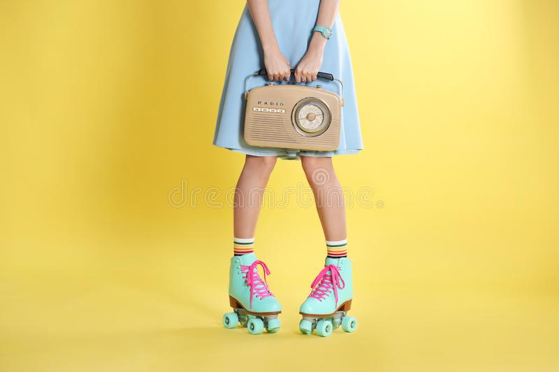Young woman with roller skates and retro radio on color background. Closeup stock photography