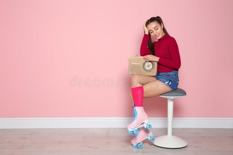 Young woman with roller skates and retro radio sitting on chair near color wall. Space for text royalty free stock photography
