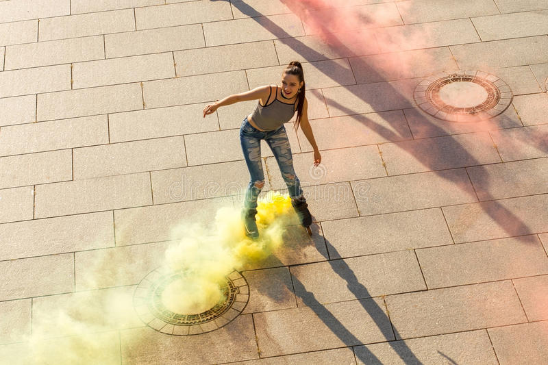 Young woman on rollerblades. Smoke coming from roller skates. Life needs more colors royalty free stock photo