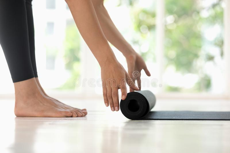 Young woman rolling black yoga mat side view close up stock photos