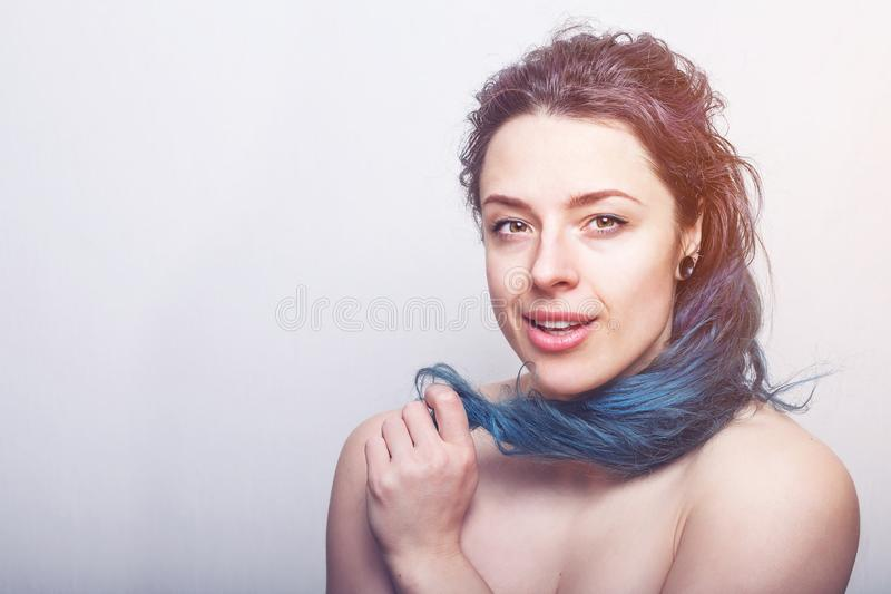 Young woman rolling her colorful but damaged messy hair on her finger. stock images