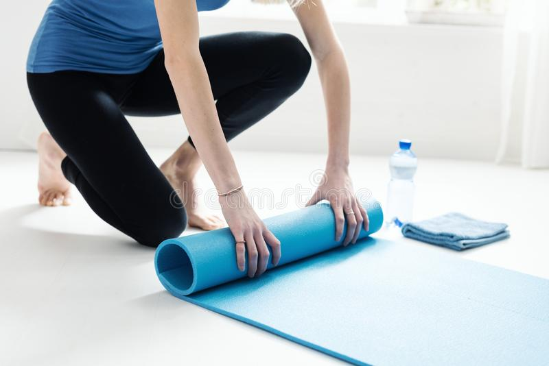 Young woman rolling her yoga mat after exercising stock photo