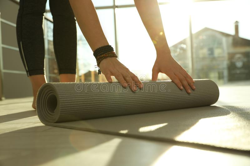 Young woman rolling yoga mat in sunlit room. Closeup royalty free stock photo
