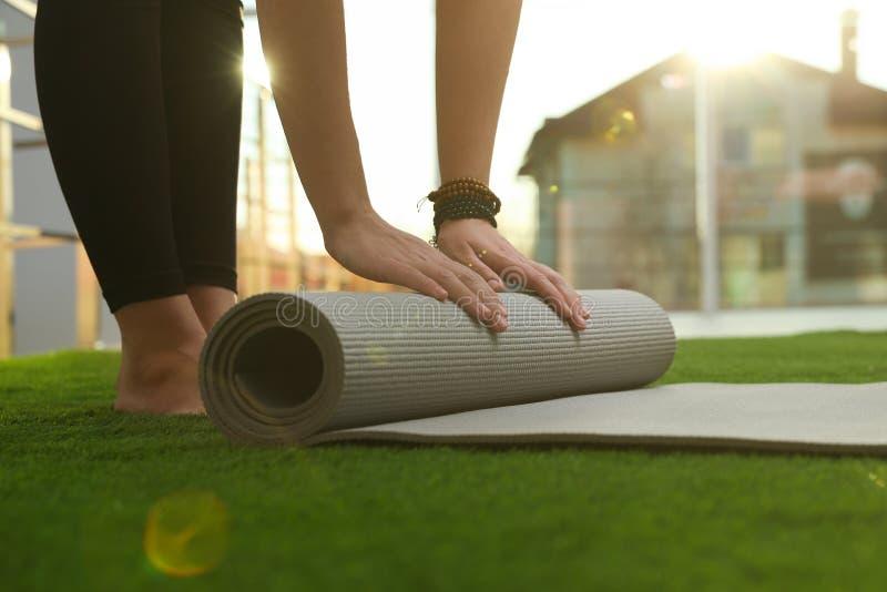 Young woman rolling yoga mat in sunlit room. Closeup stock image