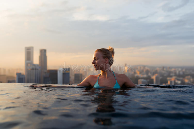 Young woman in a roof top swimming pool with beautiful city view. royalty free stock photography