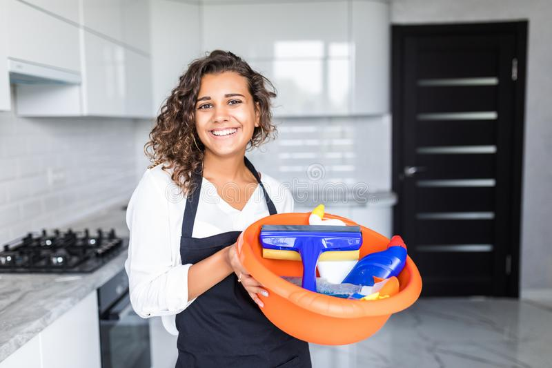 Young woman in rubber gloves holding mop and bucket with detergens. Maid cleaning at home royalty free stock photo