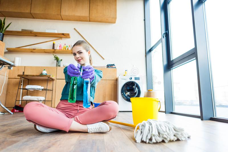 Young woman in rubber gloves holding plastic bottles with cleaning fluids and smiling. At camera royalty free stock photos