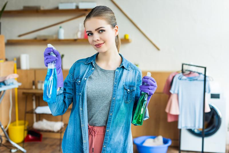 Young woman in rubber gloves holding spray bottles with cleaning fluids and smiling at camera stock image