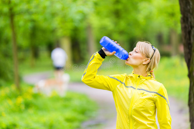 Young woman runner drinking water. Beautiful woman runner drinking water from bottle during running and walking in park, summer nature, exercising in bright stock photos