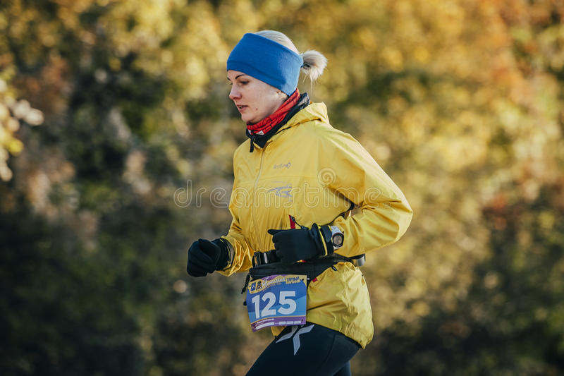 Young woman runner running in autumn forest stock photo