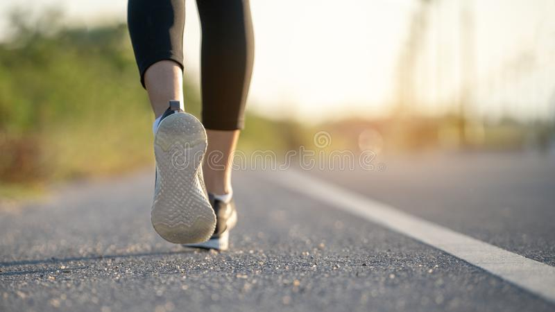 Young woman runner running on city bridge road, Young fitness woman runner athlete running at road stock photo