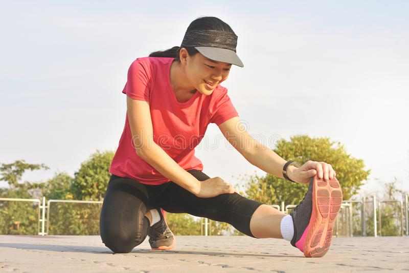 Young woman runner stretching legs before run on park royalty free stock photography