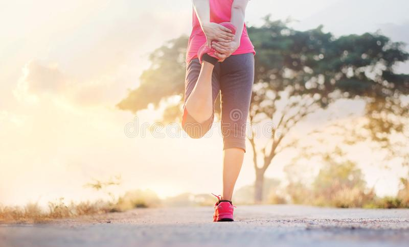 Young woman runner stretching legs before running in sunset rural royalty free stock image