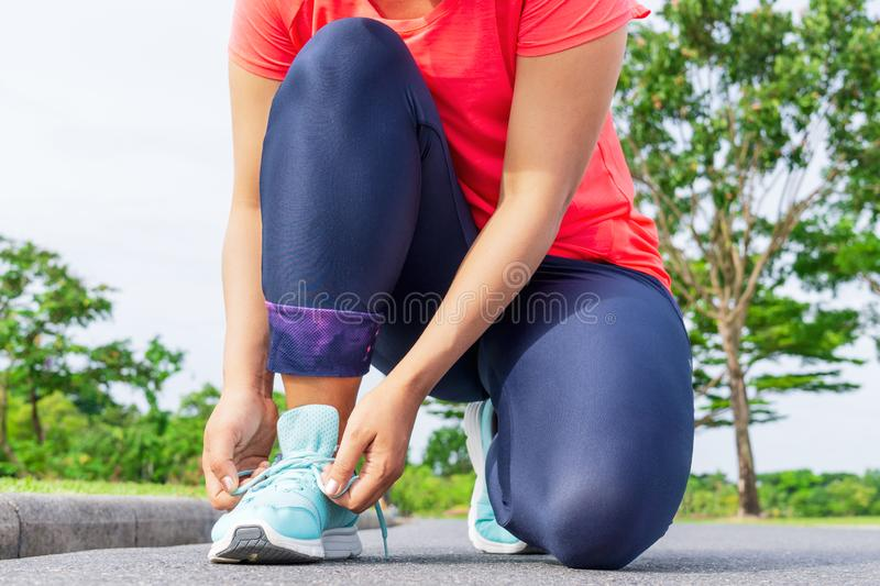 Young woman runner tying sport shoes. Preparation for the running in the public park. royalty free stock images