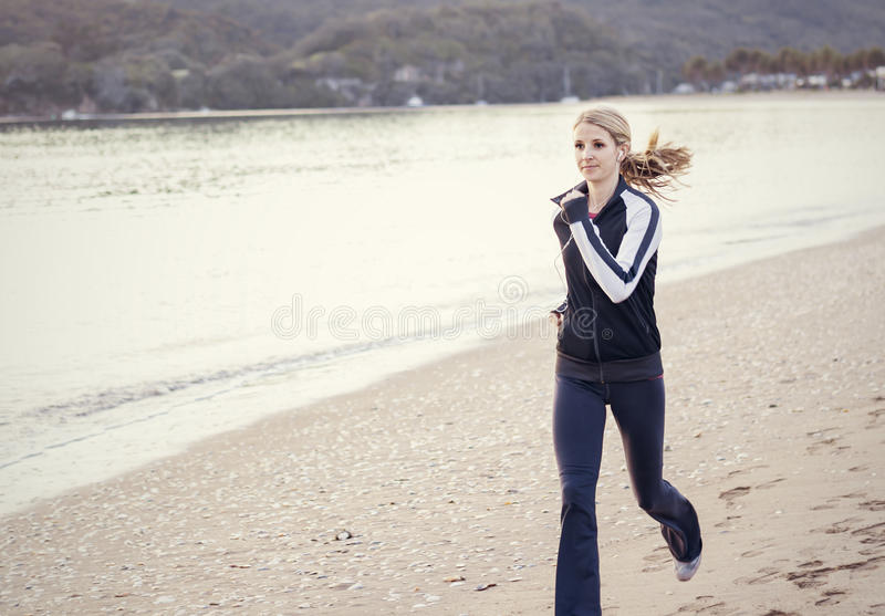 Young Woman running along the beach stock photos