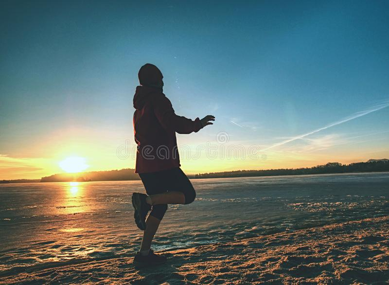 Woman running along shore of a frozen lake in winter spring. Young woman running along the shore of a frozen lake in winter spring. Regular training run, keep royalty free stock image