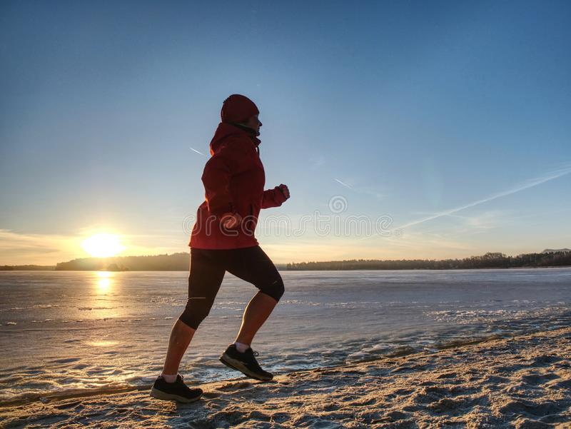 Woman running along shore of a frozen lake in winter spring. Young woman running along the shore of a frozen lake in winter spring. Regular training run, keep stock image