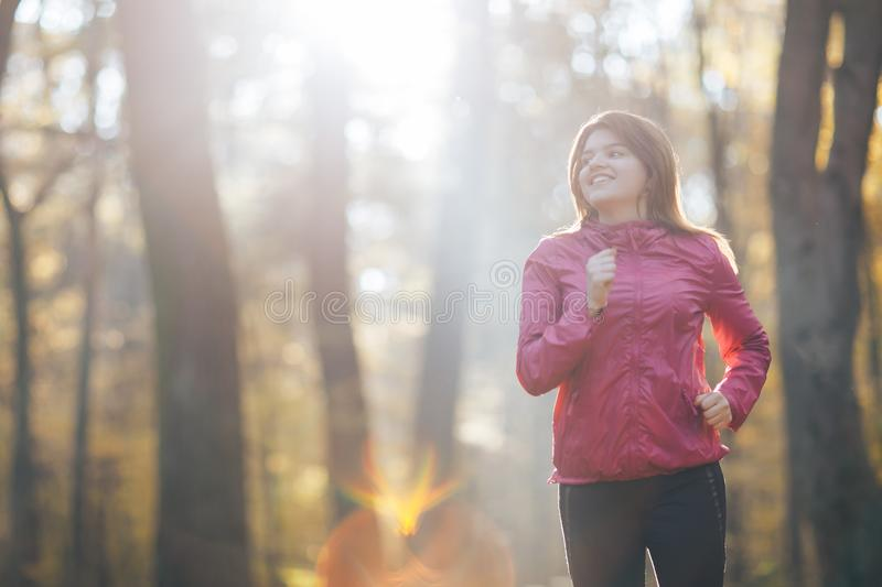 Young woman running during autumn forest stock photography
