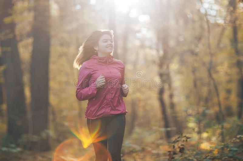 Young woman running during autumn forest stock photo