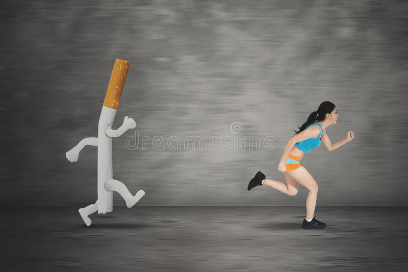 Young woman running away by a cigarette. Image of young woman running away by a cigarette with a fast motion blur background royalty free stock image
