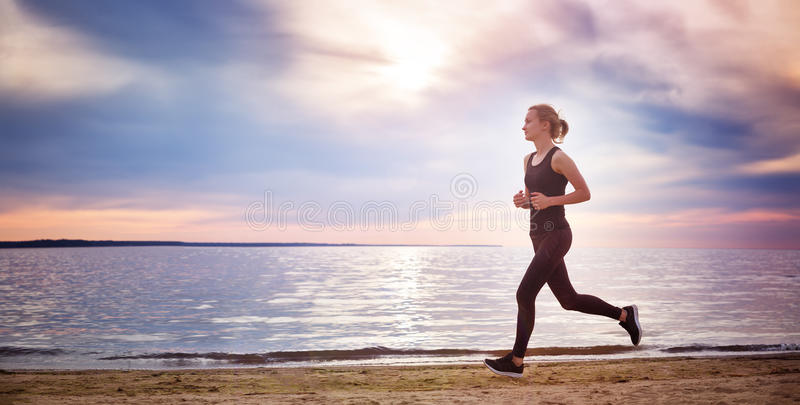 Young woman running on the beach near seaside at sunset stock photos