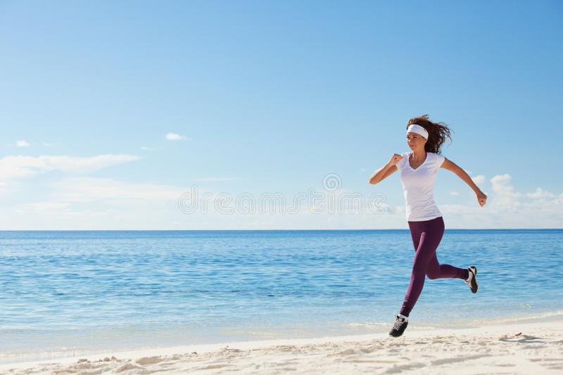 Young woman running on the beach. Summer concept. Healthy lifestyle. White sand, blue sky and crystal sea of tropical beach. royalty free stock photos