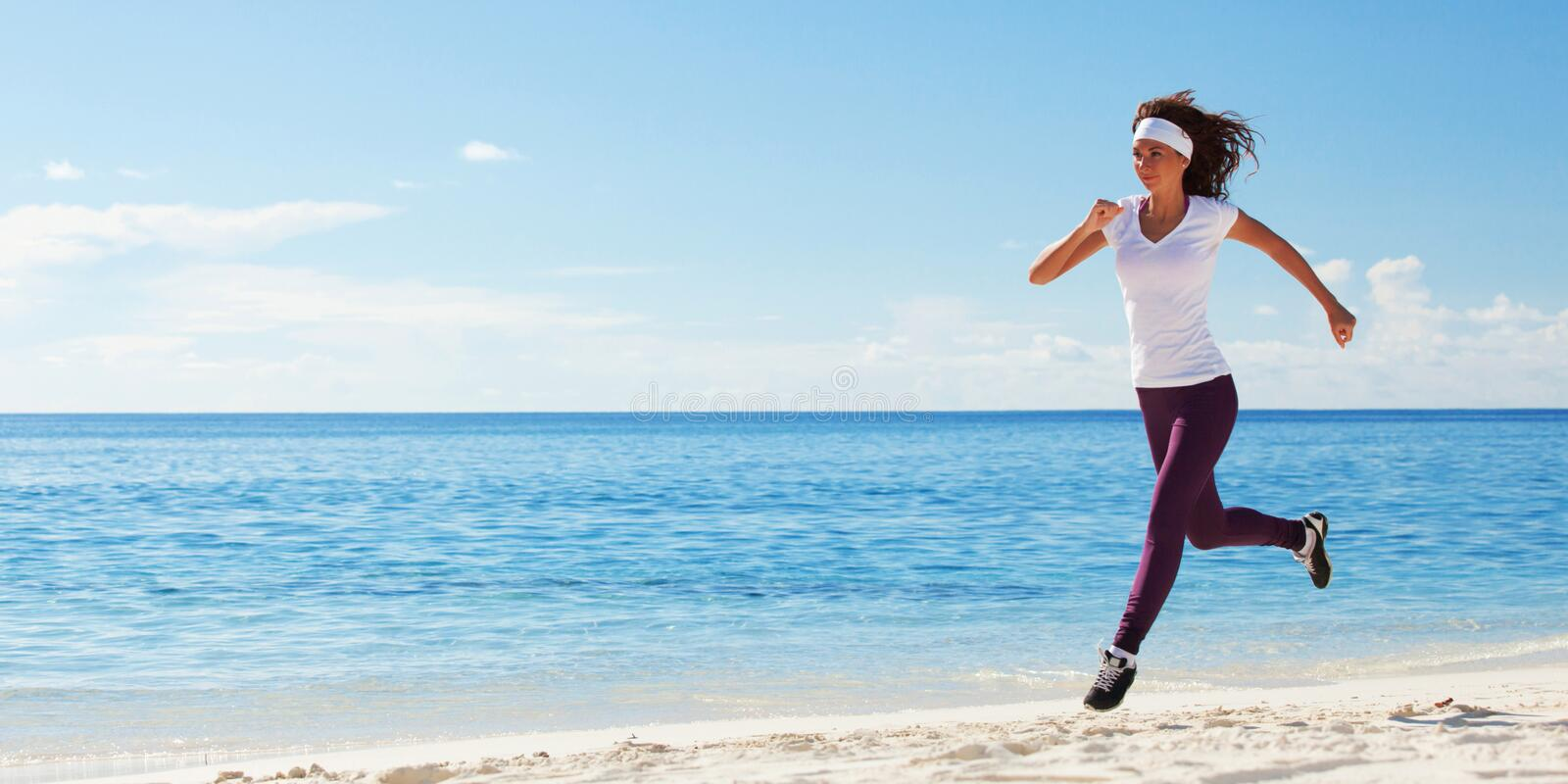 Young woman running on the beach. Summer concept. Healthy lifestyle. White sand, blue sky and crystal sea of tropical beach. royalty free stock images