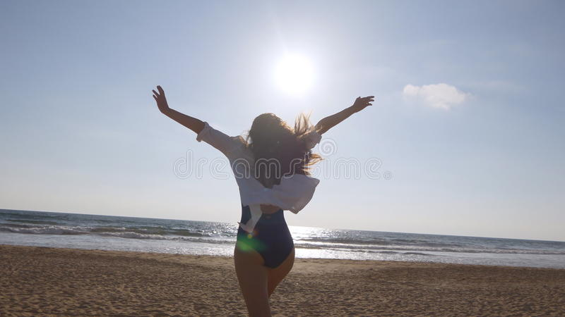 Young woman running on beach to the ocean at sunset and raised hands. Beautiful young girl going on sandy shore to the stock image
