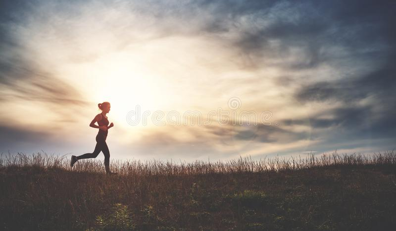 Young woman running on the field near seaside at sunset royalty free stock photo