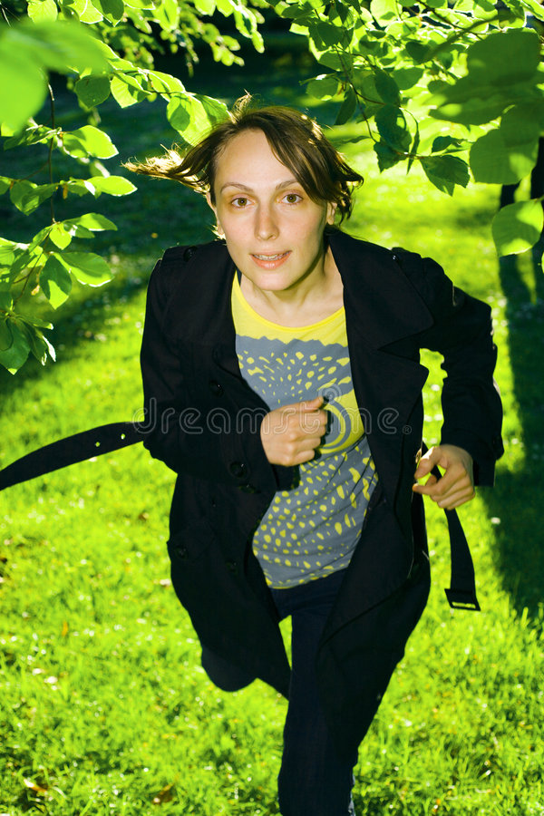 Young woman running in forest stock photography
