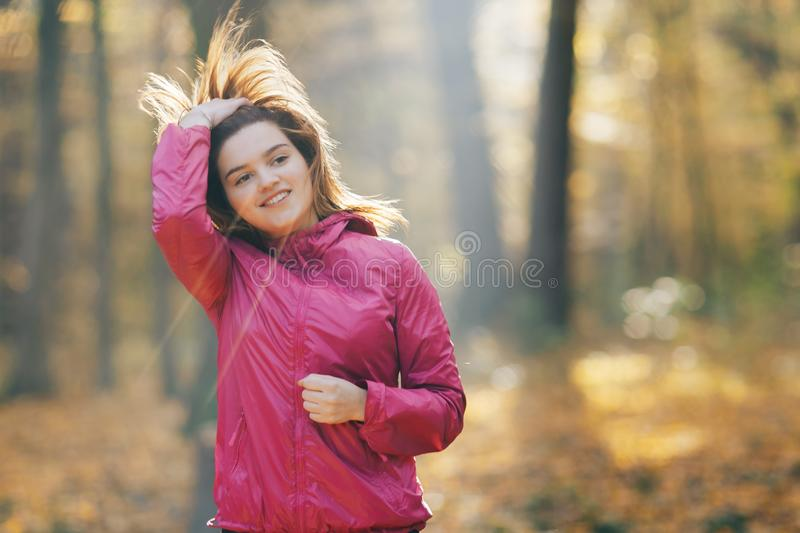 Young woman running on a forest road during sunrise royalty free stock images