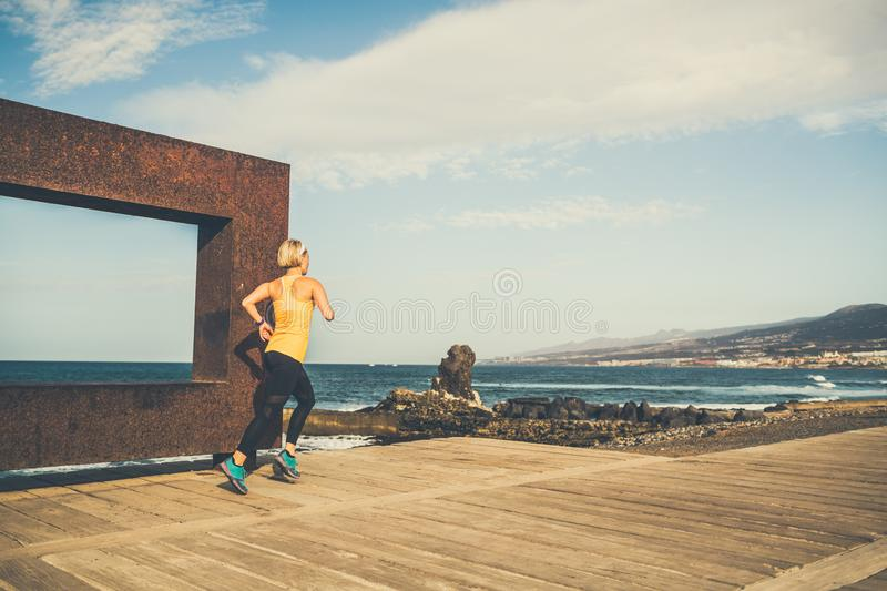 Young woman running in mountains on sunny summer day stock photos