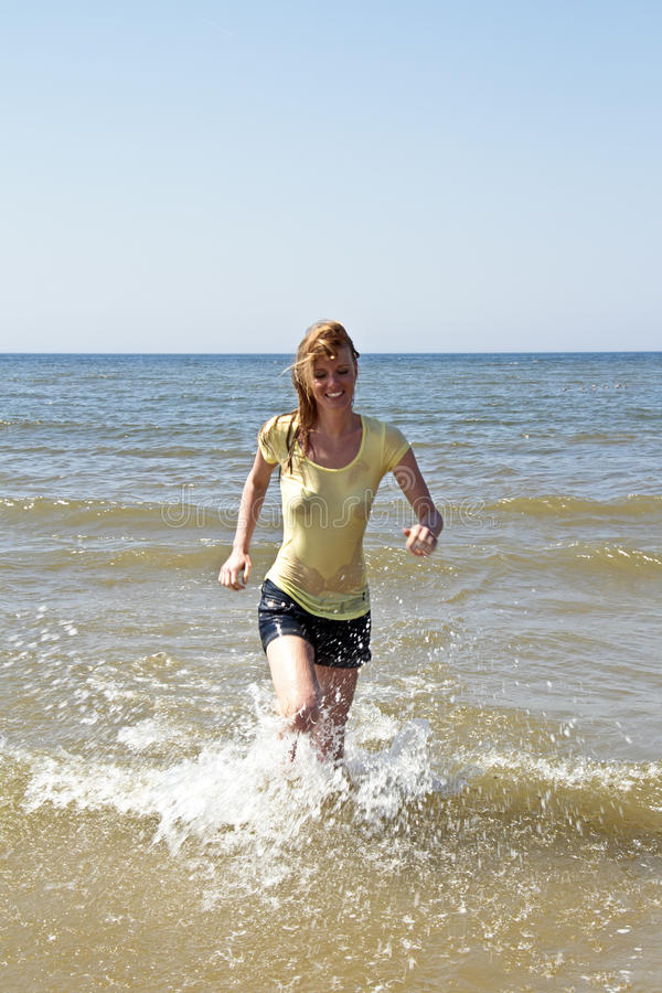 Young woman running out of the water royalty free stock photo