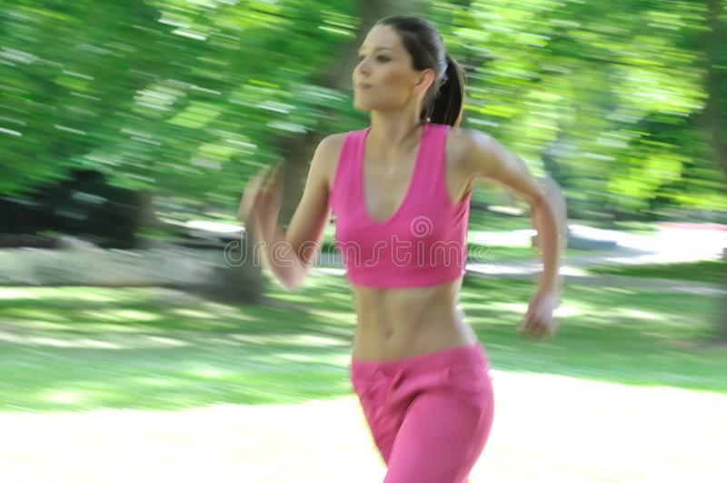 Young woman running outdoor - motion blurr. Young person (woman) running outside in park on sunny day - motion blurr stock image
