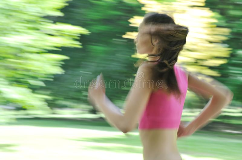 Young woman running outdoor - motion blurr. Young person (woman) running outside in park on sunny day - motion blurr stock photos