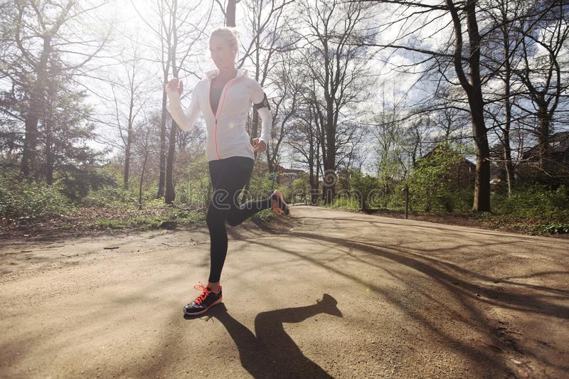 Young woman running outdoors in forest. Young caucasian woman running outdoors in forest on a sunny day. Fit female athlete jogging in a park. Caucasian female stock photos